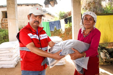 A lady receiving a baby blanket for her grandchild in Gorkha District, Nepal